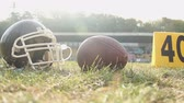 gridiron : American football helmet and ball lying on pitch, summer camp sport activities