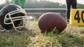 gridiron : American football players standing on pitch, ball and helmet lying on grass