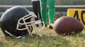 gridiron : Football helmet and ball lying on pitch, players on a break, professional sports
