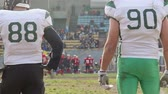 замена : Gridiron players watching active fight for ball on field, American football game