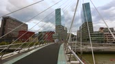 striding : Beautiful view on peaceful buildings and Zubizuri bridge in Bilbao, Spain