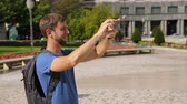 picture : Male traveller taking panorama picture of cityscape on gadget, summer vacation