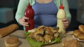 graxa : Fat lady sitting with bottles of ketchup, mayonnaise at table with roast chicken