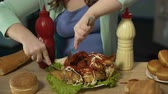 смазка : Overweight teenager carving chicken covered with ketchup and mayo and eating it