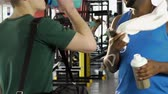 suplemento : Male friends having conversation in gym, one holding protein cocktail and phone