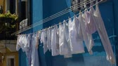 Венеция : Clean clothes fluttering in wind, hanging on bright blue colored house facade