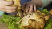 oleoso : Overweight woman tearing pieces of meat from roast chicken, eating with hands