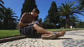 memorando : Young man sitting on lawn, writing in notebook, student making notes, education