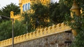 vivid wall : Small castle tower painted in yellow behind stone roofed wall, vertical panorama