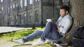 compor : Mixed-race young guy sitting under tree, taking notes in notebook, inspiration