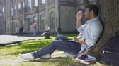 unexpected : College student sitting under tree, using laptop looking worried, upsetting news Stock Footage