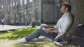 refusal : Mixed-race young guy using laptop under tree, getting bad news, disappointment Stock Footage
