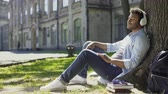 eğlenceli : Mixed young male sitting under tree in headphones, eyes closed, enjoying music Stok Video
