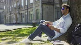 eğlenceli : Multiracial man sitting under tree wearing sunglasses, positive mood, energy