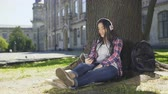 eğlenceli : Multiracial girl sitting under tree in headphones, using phone, choosing song Stok Video