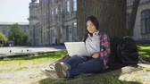 mnohorasový : Young university student using laptop, sitting under tree, smiling, socializing