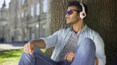 eğlenceli : Multiracial guy sitting leaning against tree in headphones, sunglasses, leisure Stok Video