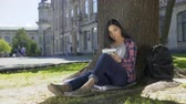 dizgi : Asian girl sitting under tree, writing fast in notebook, inspiration, poetry Stok Video