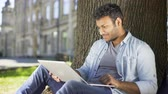 sorumluluk : Multiracial college student sitting under tree with laptop, checking final paper Stok Video