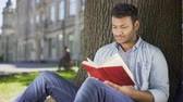 devaneio : Male reading favorite novel under tree, pressing book against chest, daydreaming Stock Footage