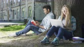 contato com os olhos : Male with book, female with laptop under tree looking at each other and smiling
