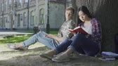çapkın : Man with laptop sitting under tree and looking at girl reading book, affection