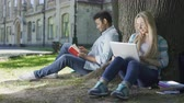 не : Young man sitting under tree with book, looking at girl with laptop, indecisive Стоковые видеозаписи
