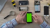 connector : Hands of technician scrolling on smartphone with green screen, diagnostics