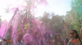 holi : Group of happy friends spraying rainbow powder paint into air, hanging out Stock Footage