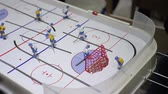 esquiador : Person playing table ice hockey, hitting puck into opposing net, indoor activity