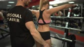 internovat : Trainer teaching woman to lift dumbbells in the gym, personal training program