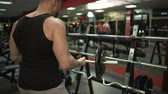 tonus : Sporty guy doing several lift-ups with curl bar, putting it back on stand in gym