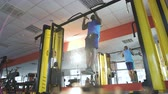 yoğun : Strong male athlete doing chin-ups in gym, working hard to have healthy fit body