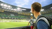 dziennikarz : Male soccer fan watching match from tribune at stadium, supporting national team