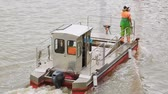 operational : Self-propelled barge going down river, carrying workers and trash bin onboard Stock Footage
