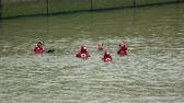 resgate : Rescue team in red jackets, helmets swimming in water getting ready for training