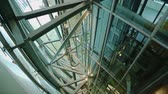 effortless : Modern metal construction of glass elevator shaft with lift going up and down