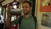 средство : Male tourist smiling and taking video of amusing scene on train with cellphone Стоковые видеозаписи
