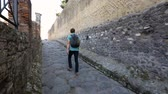 godo : Tourist going up narrow cobblestoned street between walls in Pompeii, back view