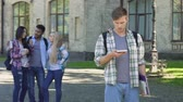 flirtovat : Sad male student scrolling on cellphone, Hispanic man flirting with females