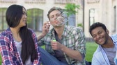 akademie : Young man lying on grass with best friends and blowing bubbles, carelessness