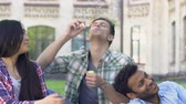 academia : Multi-ethnic group of friends relaxing near college and blowing bubbles, slow-mo
