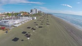 chipre : Drone flying over straw parasols standing on beach in Larnaca city, Cyprus