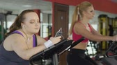 lerdo : Lazy obese girl looking at slim blonde training actively on stationary bike