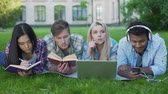 academia : Mixed-race students lying on grass and preparing for exams, university education Stock Footage