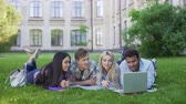 academia : Multi-ethnic students lying on grass and watching funny video on laptop, friends