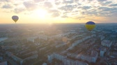 vezetett : Couple of hot air balloons floating over city against rising sun, early flights