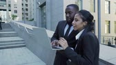 fact : Man and woman looking at laptop outside building, attorneys, brand new evidence