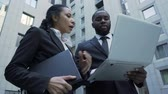 sekretarka : Afro-American businessman holding laptop, giving instructions to assistant, CEO