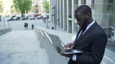 konsantre : Businessman standing outside business center, working with laptop checking files Stok Video